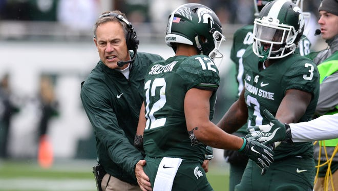 MSU head coach Mark Dantonio, left, celebrates with R.J. Shelton after Shelton's first half touchdown  against Purdue during the Spartans' 24-21 win Saturday in East Lansing