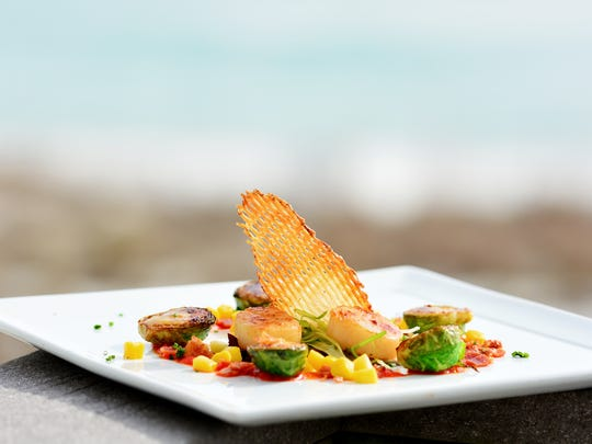 Seared Scallops with Bacon Braised Brussels Sprouts and Roasted Red Pepper Puree, courtesy of Chef Eric Troup at Margaritaville Beach Hotel.