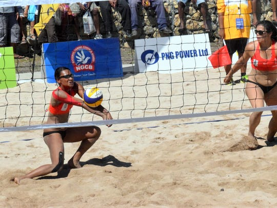 In this file photo, Guam women's national beach volleyball team member Tatiana Sablan receives a serve while teammate Kara Guerrero gets ready to set during a match against Vanuatu at the Sir John Guise beach courts at the Pacific Games in Port Moresby, Papua New Guinea.