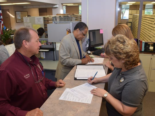 """Rapides Parish Police Jurors Joe Bishop (left foreground) and Oliver """"Ollie"""" Overton (upper left) file to run for re-election in Districts B and F, respectively, on Tuesday. Rapides Parish Clerk of Court Robin Hooter (right foreground) and Chief Deputy Clerk Janet Marcantel (behind Hooter) are handling paperwork for the candidates."""