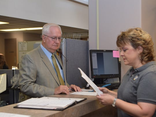 Rapides Parish Sheriff William Earl Hilton (left) qualifies Tuesday to run for re-election in the Oct. 24 primary elections. Rapides Parish Clerk of Court Robin Hooter (right), who also qualified for re-election, is handling the qualifying paperwork for Hilton.