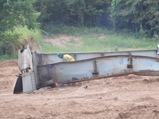 A piece of the demolished O.K. Allen Bridge is along the bank of the Red River, waiting to be cut up for scrap metal.