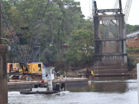 Workers continue the process of clearing pieces of the demolished O.K. Allen Bridge out of the Red River on Tuesday. The channel of the river is open to river traffic, but the removal process is expected to continue for about another week. After that, the concrete piers will be demolished and removed from the river.