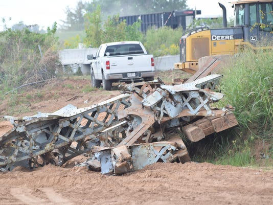 Workers continue to clear pieces of the O.K. Allen Bridge out of the Red River Tuesday.