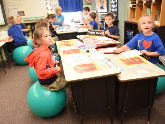 """Buckeye Elementary School first-graders Lexi Porter (left) and Harley Nelson sit on fitness balls during English language arts """"Friday Fun"""" time in Dana Anika's classroom."""