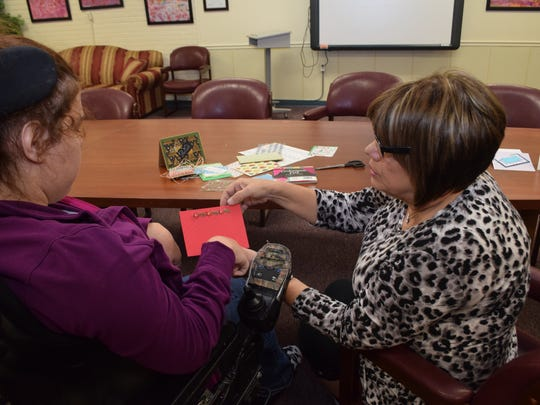 Brittany F. (left) gets help from Kay Chelette, administrative coordinator at the Louisiana Special Education Center, while putting together a Christmas card. Residents from the school made Christmas cards to sell at the Art Walk this Friday.
