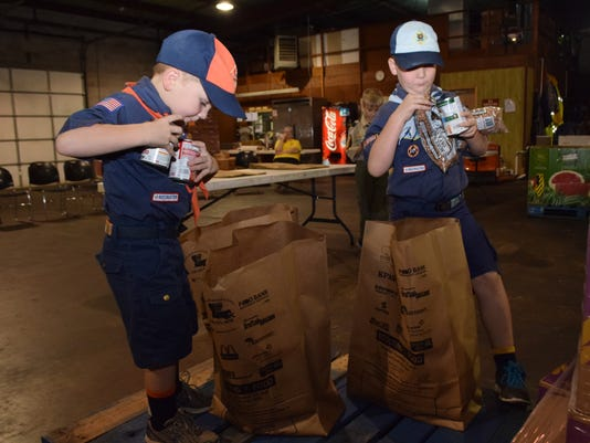 Cub Scout Pack 6 members Regan Durocher (left), a Tiger, and brother A.J. Durocher, a Bear, load items into a brown paper food bag. The bag is the same one area Scouts will distribute in neighborhoods for the 2015 Scouting for Food canned food drive. The bags will be delivered to residences on Saturday. Individuals are asked to fill the bags and place them on porches or entryways by 9 a.m. Nov. 14 for pickup by Scouts. The food will be delivered to the Food Bank of Central Louisiana.