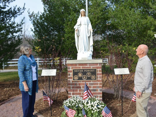 Korean War Veteran Donald Verdegan and his wife, Mary,  at a statue of Our Lady of Good Help that honors two veteran chaplains killed in the Vietnam and Korean Wars.