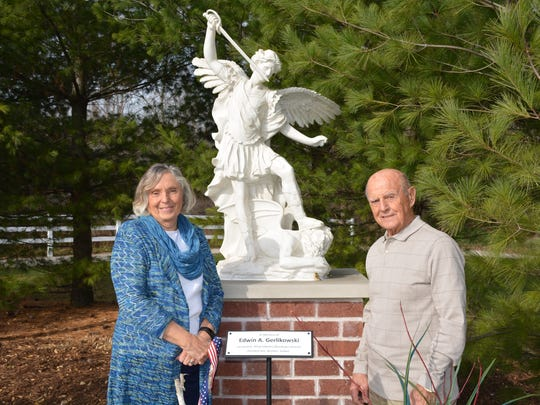 Korean War Veteran Donald Verdegan and his wife, Mary, before a statue of St. Michael the Archangel dedicated last weekend in memory of World War II veteran Edwin Gerlikowski.   Gerlikowski willed a large donation to the shrine, which he celebrated as a place of solace for his family during World War II.