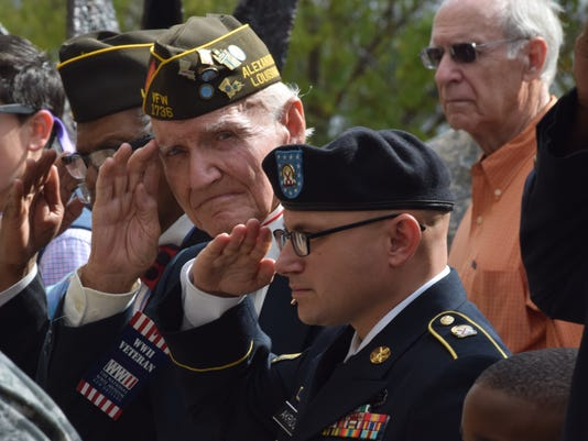 Herbert St. Romain (left), a 94-year-old World War II veteran, and Staff Sgt. Nathan Akridge who is stationed at Fort Polk, salute the posting of the colors at a Veterans Day ceremony held Wednesday at the Veterans Memorial Plaza outside of Alexandria City Hall. Both St. Romain and Akridge were guest speakers at the program. The ceremony includes a wreath laying and honored veterans of all military branches.
