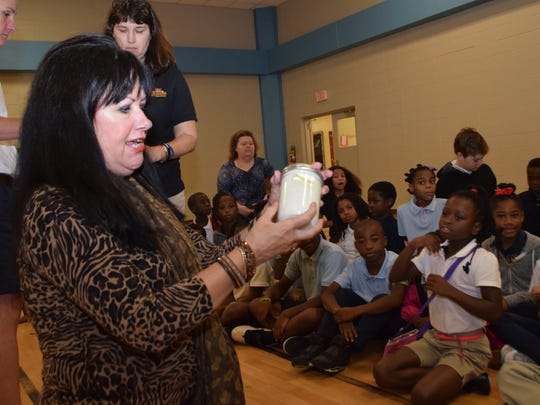 Virginia Warner, a third-grade science teacher at Mabel Brasher Elementary School, shows students how to make butter by shaking a jar of heavy whipping cream. Third-grade students were able to eat the butter on crackers along with a cabbage soup make from vegetables growing in the school's garden.