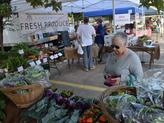 Jo Cripps looks at produce by Inglewood Farms at the Farmers' Market held in in the parking lot of First United Methodist Church Alexandria Tuesday. City of Alexandria Mayor Jacques Roy read a proclamation announcing Saturday as Food Day.
