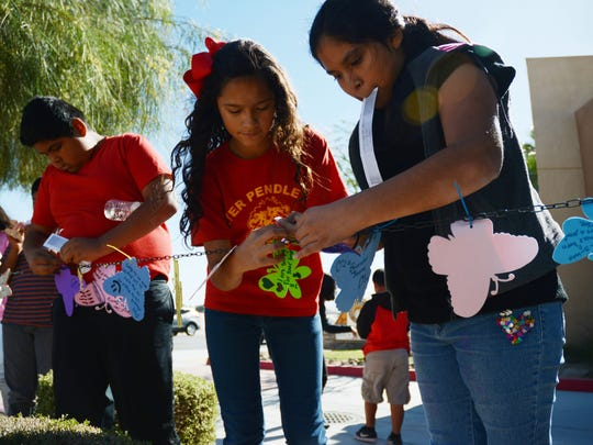 Sixth grade students from Peter Pendleton Elementary School hang their butterflies outside of the Tolerance Education Center in Rancho Mirage. Each butterfly represents the victim of a hate crime.
