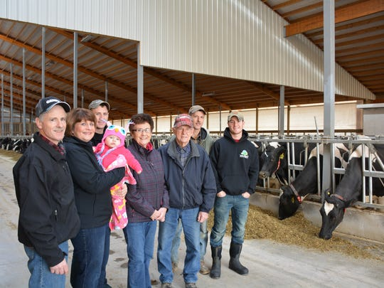 The Kinnard family, in their new barn with a new generation of farmers, represent how small- and medium-size dairy farms  are thriving.  Left to right: Dave, Anita, grandchild Abby Agamaite, Brian, Betty, Vernon, Randy and Kyler.