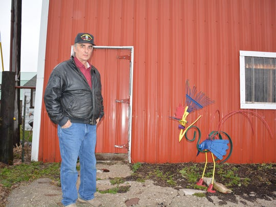 Arnie Johnsrud outside his dairy barn north of Algoma said that it is difficult for small farmers to get started today.