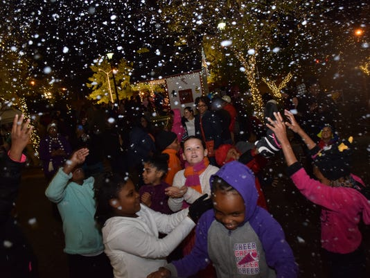 Children enjoy playing in the falling snow at Alex River Fete held Thursday in downtown Alexandria. Several snow machines are stationed at various locations.