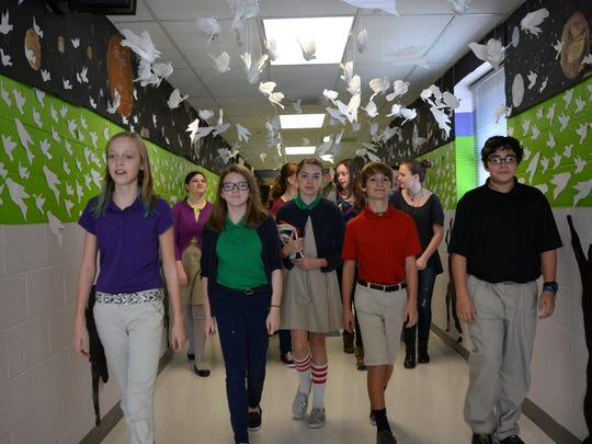 Jamie Moore's art students walk down the hallway where