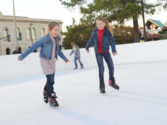Mallory Brunette (left) and Lauren Sampay skate in the outdoor ice skating rink in downtown Alexandria Friday.