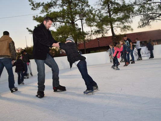 Ronnie George and daughter Addyson George skate at the outdoor ice skating rink in downtown Alexandria Friday during Alex Winter Fete.