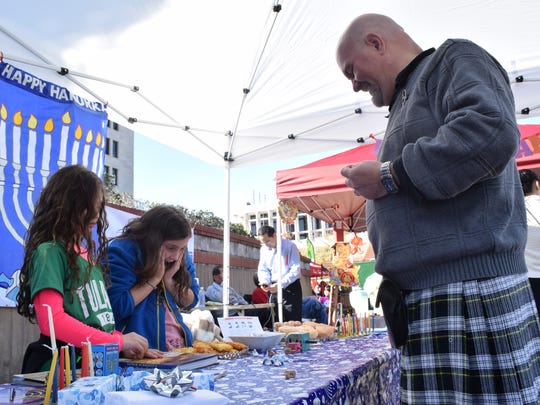 """B.B. Rubin (second from left) reacts after playing the dreidel game with Camille Kirzner (far left) and Kenn Gordon at the Jewish culture booth set up in the Cultural Village at Alex Winter Fete Saturday. Dreidel is played during Hanukkah. The dreidel has four Hebrew letters on each side, """"Nun"""" means miracle; """"Gimel"""" means great; """"Hey"""" means happened; and """"Shin"""" means there. To play the game, players each put two tokens in the center of the table. Then each person takes a turn spinning the dreidel. If the dreidel lands on """"Nun,"""" the player takes nothing nor puts nothing in the pot. If it lands on """"Gimel"""", the player takes everything in the pot and all players have to put something in the center of the table. If it land on """"Hey,"""" the player takes half the pot. If it lands on """"Shin,"""" the player has to put a token in the pot. Whoever ends up with all the tokens is the winner. Hannukah begins tomorrow."""