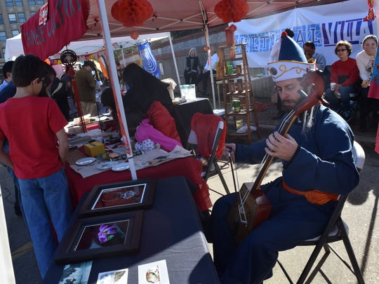 """Matthew Stokes plays a Mongolian horse head fiddle or a """"Matouqin"""" at the Chinese culture booth set up in the Cultural Village at Alex Winter Fete Saturday. Stokes said the """"Matouqin"""" is a traditional Mongolian instrument."""