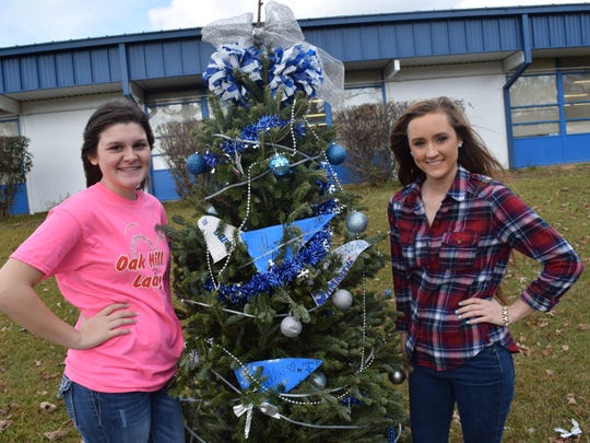"Oak Hill High School seniors Kristen Brister (left) and Bailie Cooper stand next to a Christmas tree they decorated with their fellow cheerleaders for a contest started by Christine ""Honey"" Belgard, art teacher at the school. About 14 trees were decorated by different school organizations and will be judged Wednesday."