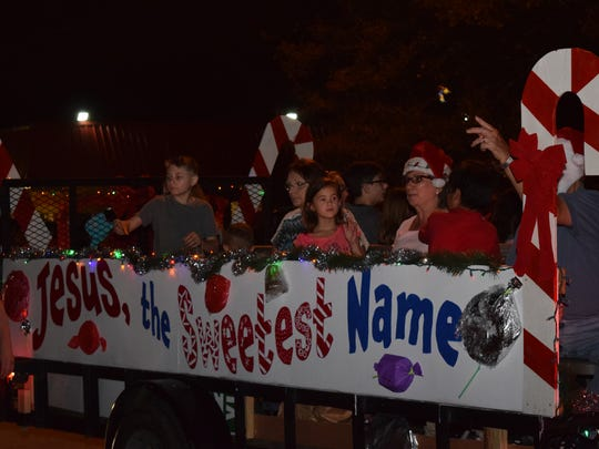 Riders on the Christian Challenge float wave to parade-goers as they pass by in the Pineville Christmas Parade held Friday.
