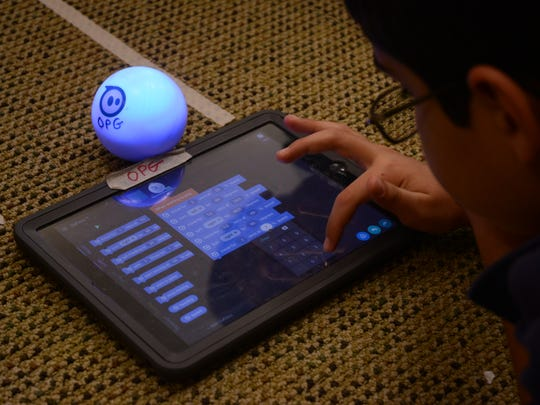 A student at Palm Valley School, a private school in Rancho Mirage, codes a Sphero to direct it through a series of mazes.