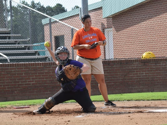 ANI LC Softball camp Erica Harwell (back), a former Louisiana College softball star and now head coach of the Alexandria Senior High softball team, watches Montgomery's Hannah Vercher as she catches during the Louisiana College Elite Softball Clinic held Tuesday, July 7, 2015.-Melinda Martinez/The Town Talk