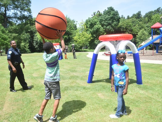 ANI Rec2U City of Alexandria Police officer Cpl Anthony Gillard (far left), Jaylen Davis and D'Kia Leach play kid basketball Harmon Park located on Monroe Street. During the summer the City of Alexandria Community Services Department will host a mobile rec