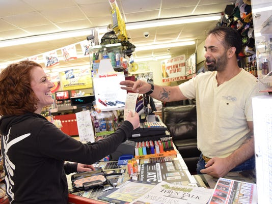 Roy Mashni (right), owner of Super Al's convenience store on the corner of Jackson Street and Texas Avenue, hands Shana Prince a Powerball ticket she bought at his store Friday.