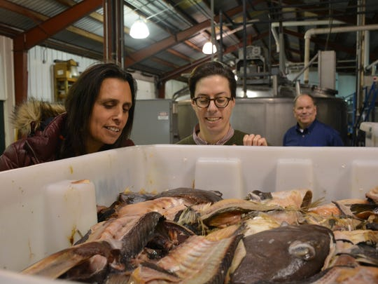 """Winona LaDuke and Hans Dramm examine fish scraps in Dramm's Algoma facility. """"This is the future of American agriculture,"""" said LaDuke. """"Our people put fish on their crops for many centuries and American agriculture is learning to go back to putting natural things on their crops."""""""
