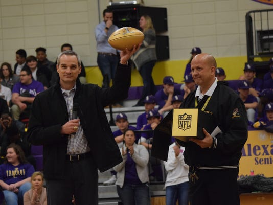 Chris Boniol (left), former kicker for the Dallas Cowboys and 1989 Alexandria Senior High School alum, holds up a gold football given to Alexandria Senior High School from the NFL as ASH principal Duane Urbina holds the box it came in. The NFL is honoring high schools who've had alumni play in the Super Bowl with gold football. The event is being done in celebration of the 50th anniversary of the Super Bowl.