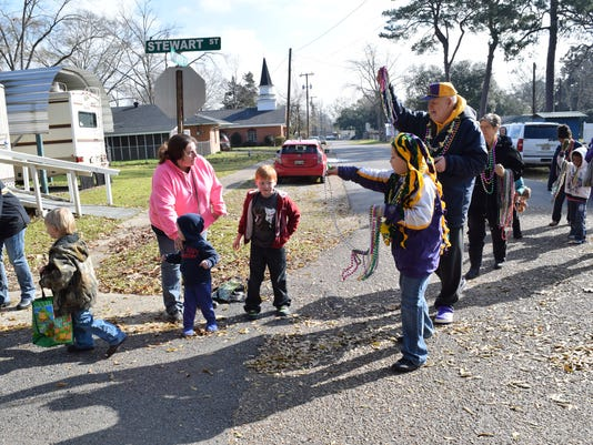 Dylan Scott (front, far right) , grandson of Pollock mayor Jerome Scott (back, right), hand out beads during the 11th annual Pollock Children's Mardi Gras parade held Saturday in Pollock. The parade started in Foster Park and wound around the neighborhood for a few blocks.