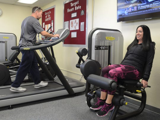 P.E. teacher Matt Amrine (left) and P.E. and nutrition teacher Tanya Niwa (right) try out the machines at Cielo Vista Charter Schools new community fitness center. The fitness center is open to family. students and staff at the school.