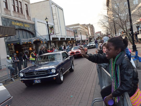 Jamaica Bell asks for throws as she watches the Hixson Classic Cars & College Cheerleaders Parade as it passes down Third Street in downtown Alexandria on Friday.