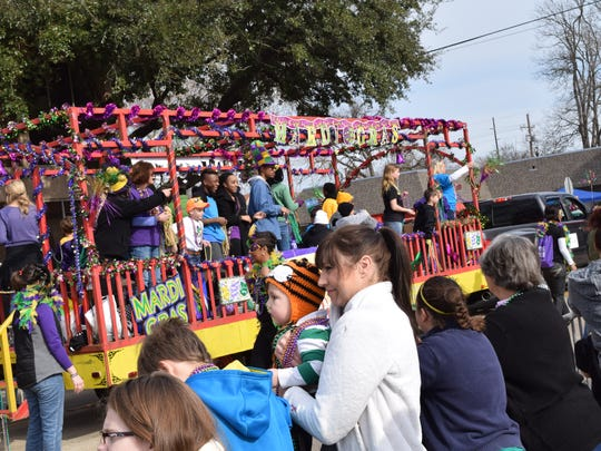 Parade-goers watch the Children's Mardi Gras Parade Saturday in downtown Alexandria.