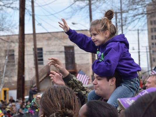 Kathleen Schoolcraft sits on her brother Joey Schoolcraft's shoulders to catch throws as they watch the Children's Mardi Gras Parade Saturday in downtown Alexandria.