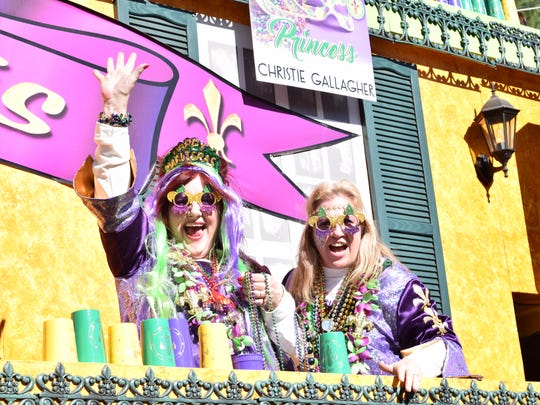 Krewe of Fleur de Lis members wave to parade-goers at the 23rd annual krewes parade Sunday in Alexandria.