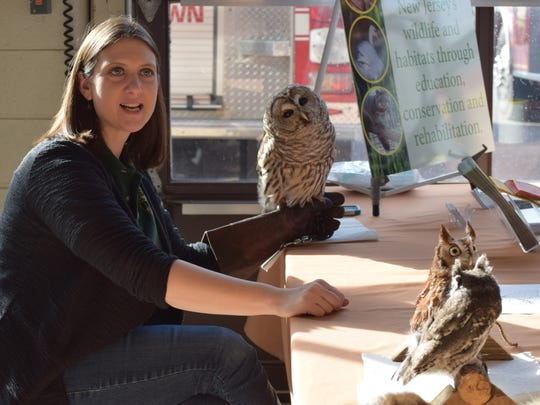 Denise Peters, director of Education at the Cedar Run Wildlife Refuge in Medford, talks to visitors at the Cumberland County Winter Eagle Festival as she handles a barred owl. Two live screech owls are perched on the table in front of her. More than 40 exhibitors and merchants were set up at the Mauricetown Fire Hall for the annual event. Photo/Jodi Streahle