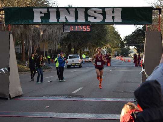 Matt Meizereck, 24, is the first runner to cross the half marathon finish line.