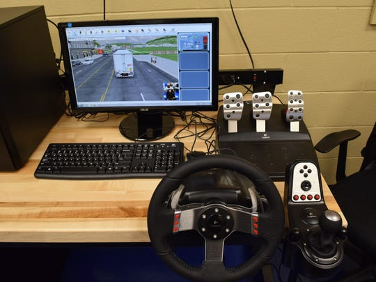 Ramon Milano (right), instructor for the Commerical Driver's License program at Central Louisiana Technical Community College, can create scenarios for students from these controls as they drive the new truck driving simulator at CLTCC.