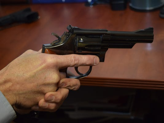 Rapides Parish Sheriff's public affairs officer Tommy Carline holds a .38 caliber handgun.