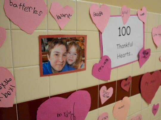 A photo of Mary Linn Bergstrom, left, with her daughter Chloe was one of several hung in the hallway of Deposit Elementary School Thursday for the event Brownies for Breakfast.