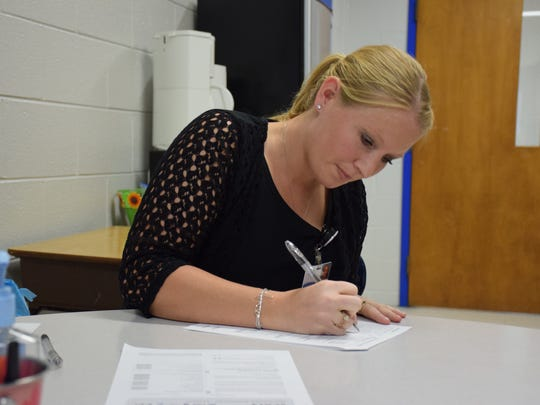 Liz Landes, left, a senior nursing student at Eastern Mennonite University, writes down answers from a Fort Defiance football player during his baseline concussion screening Tuesday at Fort Defiance High School.