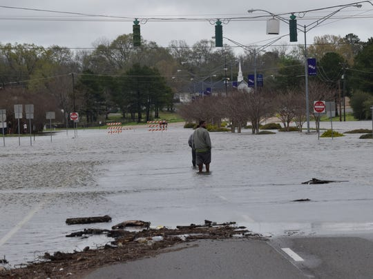 People wade in the floodwaters at the intersection of Highway 1 and Highway 6  in Natchitoches Thursday. The intersection was closed due to flooding.