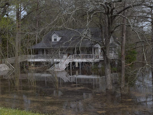 A house located on Highway 107 sits above water surrounding it.