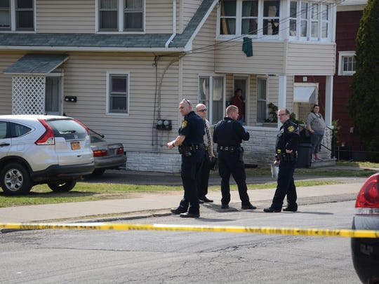 Police officers investigate a shooting on Corliss Avenue in Johnson City, between Albert and Allen streets.