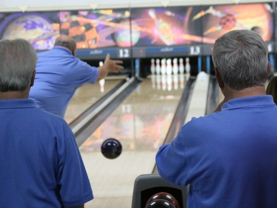 Two men watch their teammate go for a strike at Cherokee Lanes, soon to be SouthBound Alley's league bowling night.
