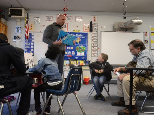 Joel Davis, a former Binghamton High School football player and starting Tight End at the West Point Preparatory School, reads to students at Theodore Roosevelt Elementary School Wednesday.